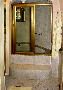 ample cabinets and a unique step up shower room of generous proportions with a deep tub you can lounge and luxuriate in to your hearts delight ample shower room